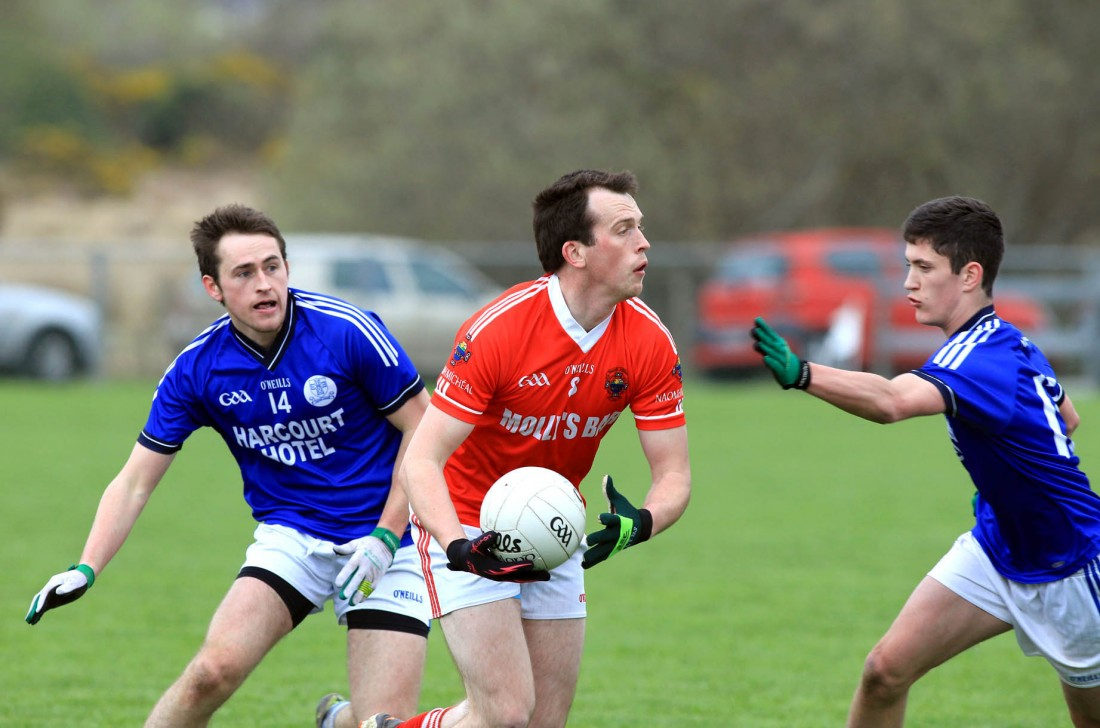 Michael McGinley, St Michaels in possession against AJ Gallagher and Ethan O'Donnell of Naomh Conaill.